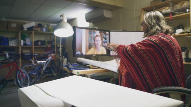 der reife mann arbeitet im home office mit architekturzeichnungen und hat eine videokonferenz und mit einem smartphone die zeichnungen seinem kollegen am abgelegenen ort, einer frau mittleren alters, zeigen. - 50 54 years stock-videos und b-roll-filmmaterial