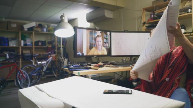 der reife mann arbeitet im homeoffice mit architekturzeichnungen und hat eine videokonferenz mit seiner kollegin - mitarbeiterin, einer frau mittleren alters. zeigen sie ihr die zeichnungen, indem sie dokumente vor der webcam halten. - 50 54 years stock-videos und b-roll-filmmaterial