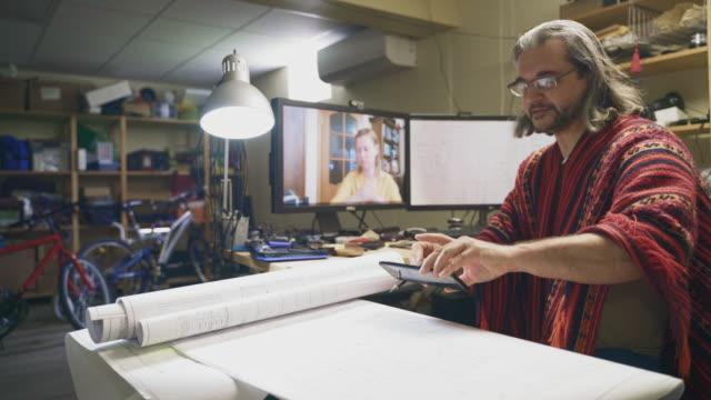 der reife mann arbeitet im home office mit architekturzeichnungen und hat ein video-meeting und mit einem smartphone, um die zeichnungen seinem kollegen am abgelegenen ort, einer frau mittleren alters, zu zeigen. - 50 54 years stock-videos und b-roll-filmmaterial