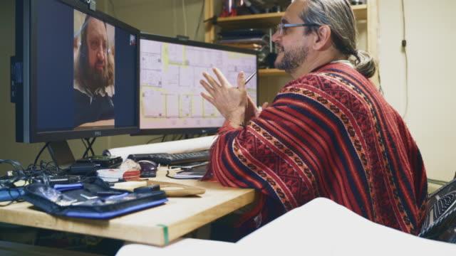 der reife mann, der ingenieur, arbeitet im homeoffice mit architekturzeichnungen, hat eine telefonkonferenz mit seinem kollegen, einem mann mittleren alters. - 50 54 years stock-videos und b-roll-filmmaterial