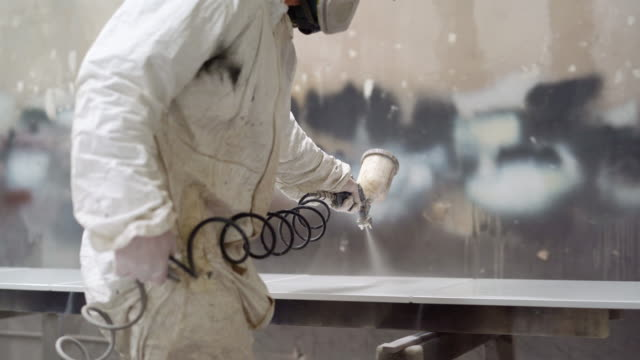The mature man wearing protective mask and coveralls painting the furniture's details at the small manufacture