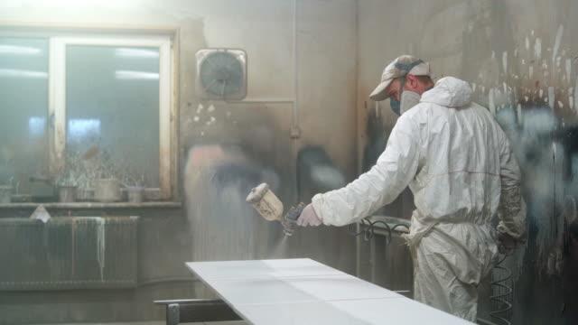 Der ältere Mann trägt Schutzmaske und Overalls, die Malerei der Möbel Details der kleinen Manufaktur