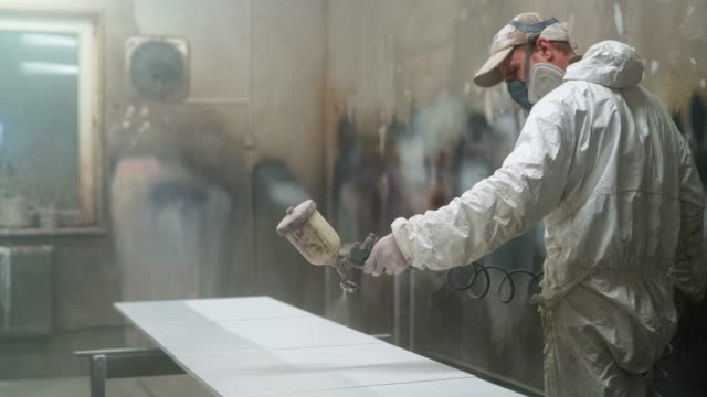 the mature man wearing protective mask and coveralls painting the furniture's details at the small manufacture - spraying stock videos and b-roll footage