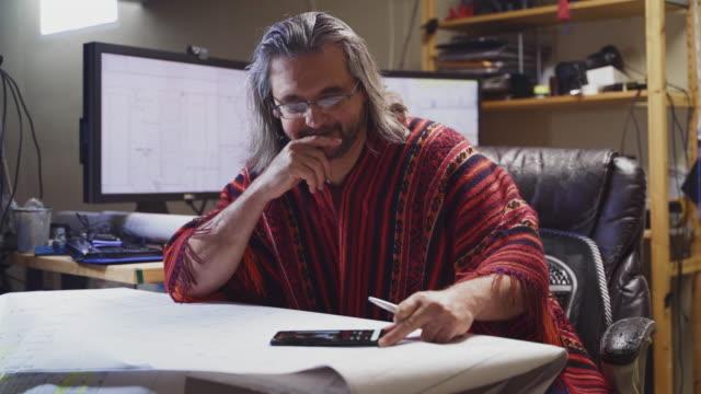 赤いポンチョを着ている成熟した男性は、建築の図面を扱い、地下室にあるホームオフィスでスマートフォンを使用しています。 - 50 54 years点の映像素材/bロール