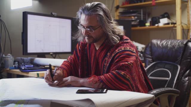 der reife mann, der einen roten poncho trägt, arbeitet mit architekturzeichnungen und benutzt ein smartphone im home office in einem keller, überprüft zeichnungen, macht notizen. - 50 54 years stock-videos und b-roll-filmmaterial