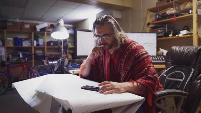 der reife mann, der einen roten poncho trägt, arbeitet mit architekturzeichnungen und benutzt ein smartphone im home office in einem keller. - 50 54 years stock-videos und b-roll-filmmaterial