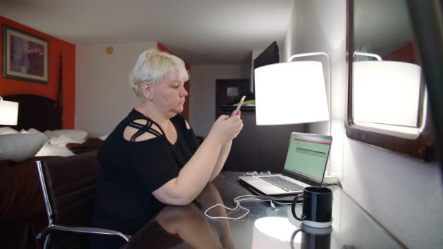 the mature woman working online with the laptop from the motel room - blonde hair stock videos & royalty-free footage