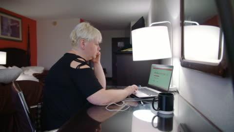 den mogna kvinnan arbetar online med den bärbara datorn från motell rummet - 45 49 år bildbanksvideor och videomaterial från bakom kulisserna