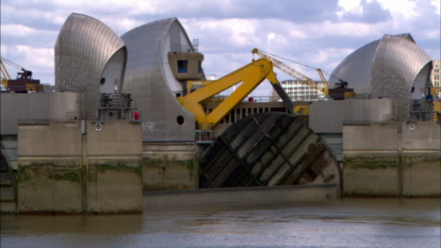 the mechanical arm of the thames barrier pulls up a wall in the river thames to block flood water. - block shape stock videos & royalty-free footage