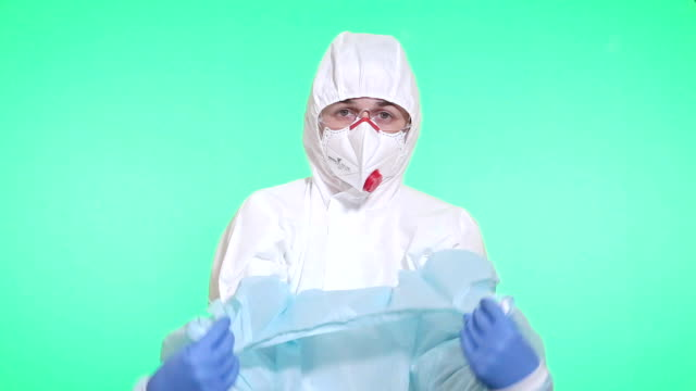 the medical professional removes an operating gown. - lab coat stock videos & royalty-free footage