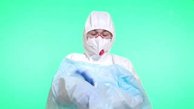 the medical worker puts on an operating gown. - operating gown stock videos & royalty-free footage