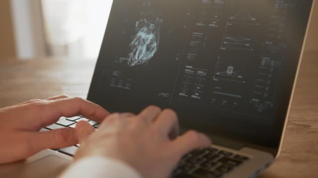 der mediziner analysiert die daten des medizinischen scanners auf dem laptop. - diagramm stock-videos und b-roll-filmmaterial