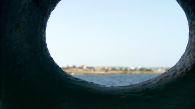 The Mediterranean coastline is seen through a porthole. Available in HD.