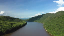 The Mekong river crosses the countryside surrounded by mountains and green forests in Laos, Luang Prabang, in summer and by drone during a day under the Sun.