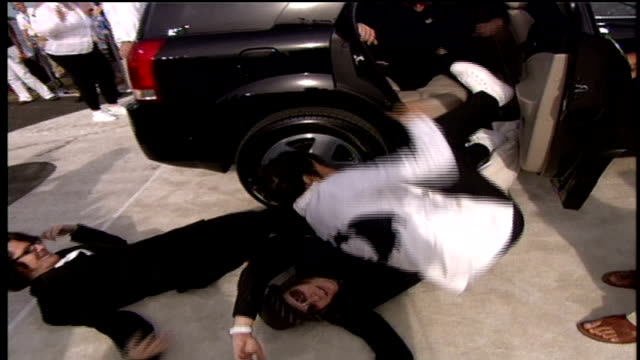 The members of Fall Out Boy literally falling out of their car and then walking down red carpet while interacting with fans