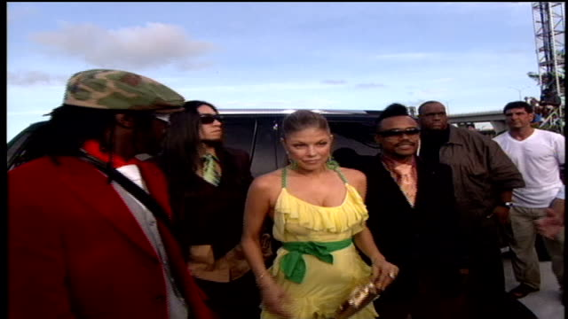 the members of the black eyed peas greeting and posing for photos with fans while walking down red carpet - the black eyed peas band stock videos and b-roll footage