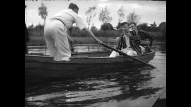 the men, one smoking a pipe, precariously get into the rowboat, row away. - colonial stock videos & royalty-free footage