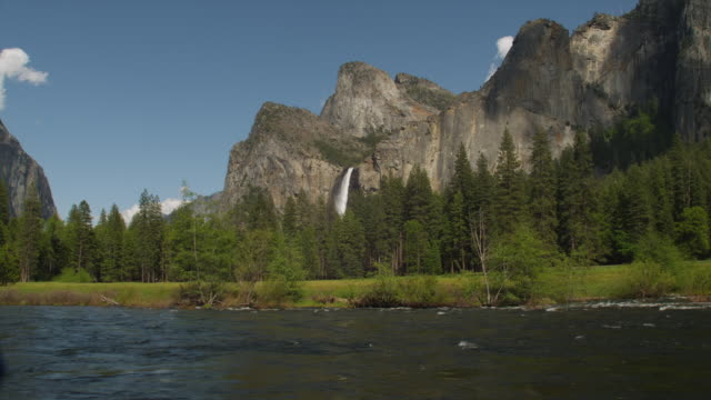 the merced river flows past mountains in yosemite national park, california. - merced fluss stock-videos und b-roll-filmmaterial