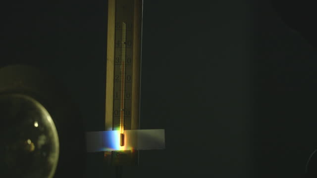 vídeos de stock, filmes e b-roll de the mercury on a wooden thermometer slowly rises from 28 to over 50 degrees celsius as it measures the temperature of refracted light. - mercúrio metal