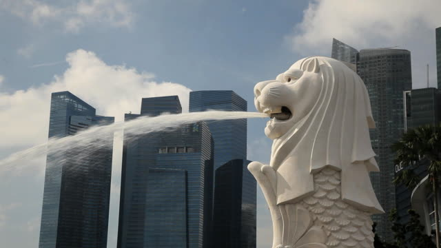 the merlion statue with the city skyline in the background, marina bay, singapore, south east asia - merlion fictional character stock videos and b-roll footage