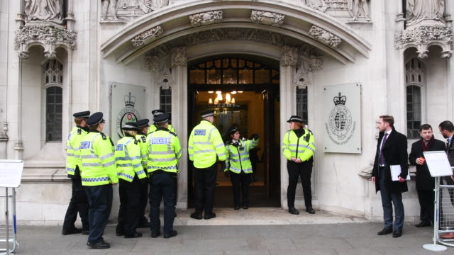 the met police stand on guard in front of the supreme court in london on december 6th 2016 the eleven supreme court justices are hearing the... - corte suprema palazzo di giustizia video stock e b–roll