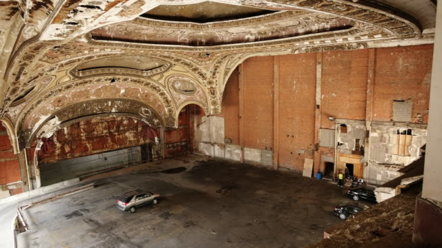 the michigan theatre in the michigan building in detroit is now a parking garage. extreme wide shot of car parked under  neo-gothic plasterwork - spoonfilm stock-videos und b-roll-filmmaterial