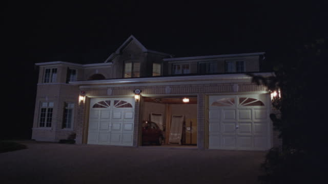 the middle door closes on a large house with a three car garage. - garage video stock e b–roll