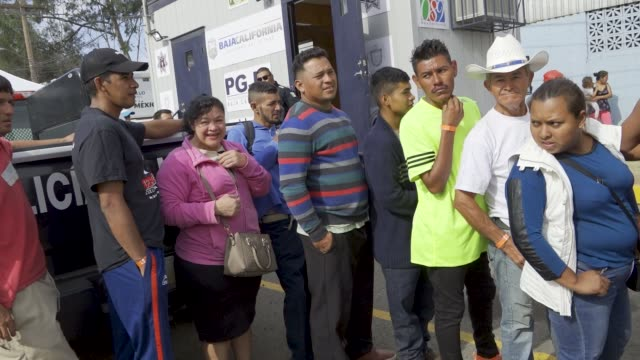 the migrant caravan people stand in line to be driven by bus to a job - employment fair in tijuana, mexico to assess their skills for possible... - 就職フェア点の映像素材/bロール