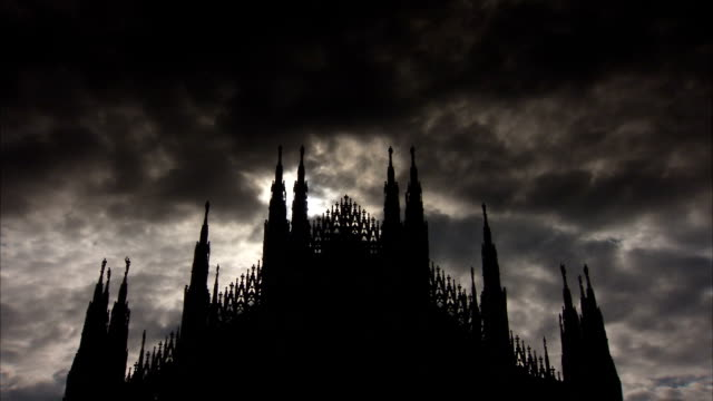 the milan cathedral is silhouetted against a dark cloudy sky at dusk. available in hd. - spira tornspira bildbanksvideor och videomaterial från bakom kulisserna
