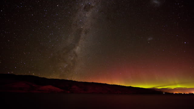 ws t/l the milky way and aurora australis appear behind the dunstan range / central otago, new zealand - paranormal stock videos & royalty-free footage