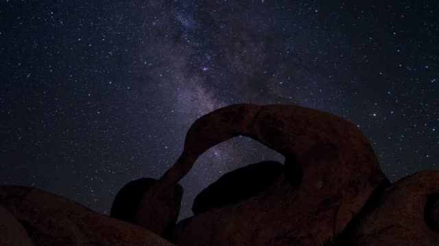 The Milky Way galaxy moves over an ancient rock arch in the Alabama Hills of California.