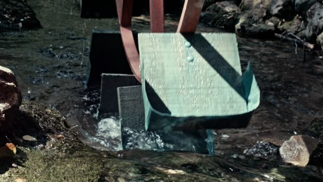 the mill wheel rotates under a stream of water - water wheel stock videos and b-roll footage