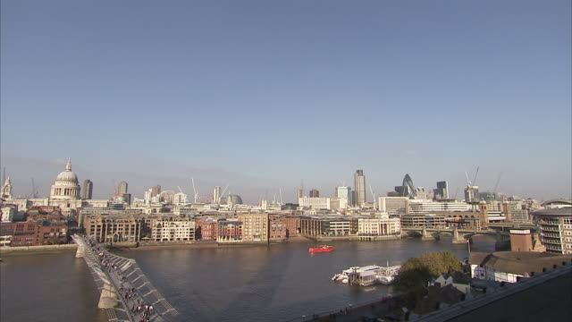the millennium bridge crosses the river thames to st. paul's cathedral. available in hd. - london millennium footbridge stock videos and b-roll footage