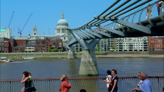 the millennium footbridge spans the thames river in london, england. - london millennium footbridge stock videos & royalty-free footage