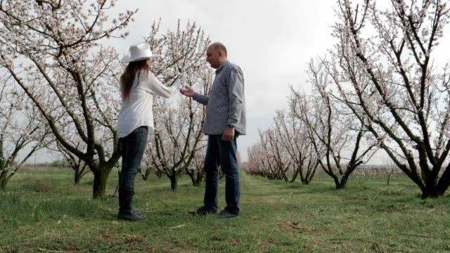 The Modern Farmer, Slow motion of a Young Cheerful Entrepreneurs Walking In An Orchard, Using Digital Tablet. Springtime, Agricultural Occupation, Small Business, Investment, Innovation, Woman Leader Working, Using Technology, Outdoors.