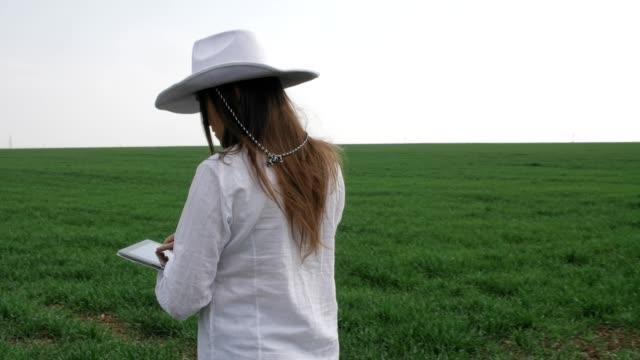la donna contadina moderna, al rallentatore di un giovane allegro imprenditore che cammina in un campo di grano, usando tablet digitale. primavera, occupazione agricola, piccole imprese, investimenti, innovazione, donna leader lavorando, utilizzando la tec - sunny video stock e b–roll