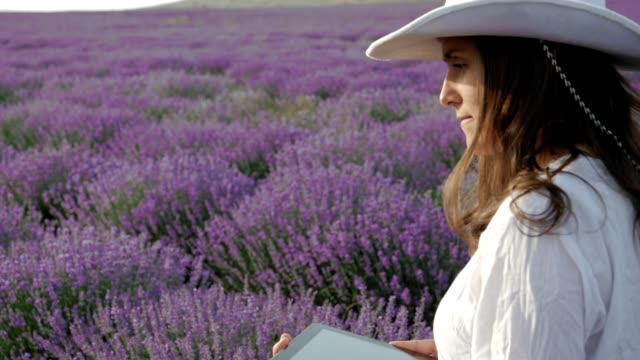 The Modern Farmer Woman Walking In her Lavender Field Using Digital Tablet. Small Business, Agricultural Occupation and Investment in Innovations and Technology.