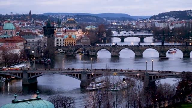 The Moldau River flows under bridges including the Charles Bridge in the city center at twilight on December 25 2018 in Prague Czech Republic Prague...