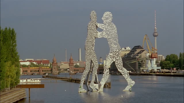 the molecule man sculpture rises from the spree river in berlin, germany. - スプリー川点の映像素材/bロール