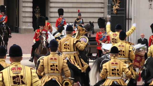 vidéos et rushes de the monarch queen elizabeth reviews her guards on her official birthday, as they march and ride past her as she stands outside at buckingham palace in london. - angleterre