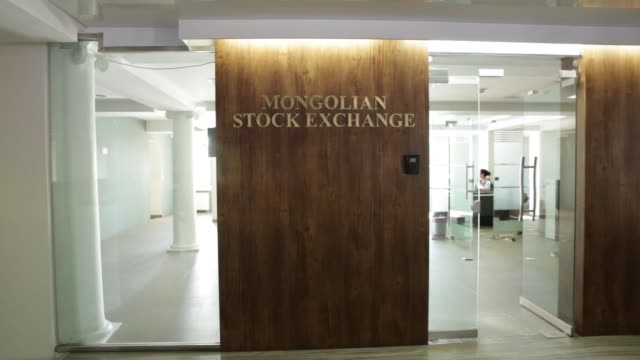 The Mongolian Stock Exchange stands in Ulaanbaatar Mongolia on Tuesday July 19 Pedestrians walk past signage displayed at the Mongolian Stock...