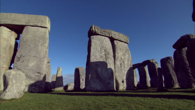 the monolithic stones of stonehenge cast long shadows under a blue sky. - obelisk stock videos & royalty-free footage