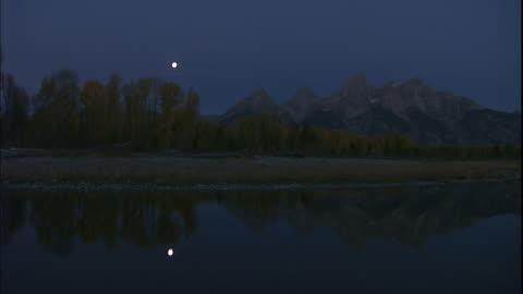 the moon and teton range reflect in a lake. - teton range stock videos & royalty-free footage