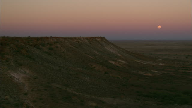 the moon glows above a vast australian plain. - coober pedy stock videos & royalty-free footage