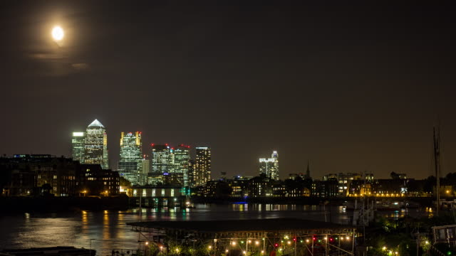 The moon glows in the sky above Canary Wharf.