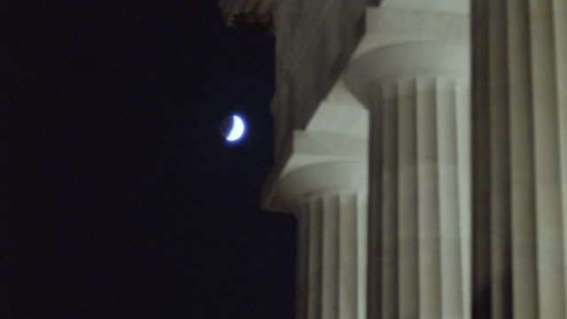 the moon hangs in the sky over the columns of the lincoln memorial. - monument stock videos & royalty-free footage
