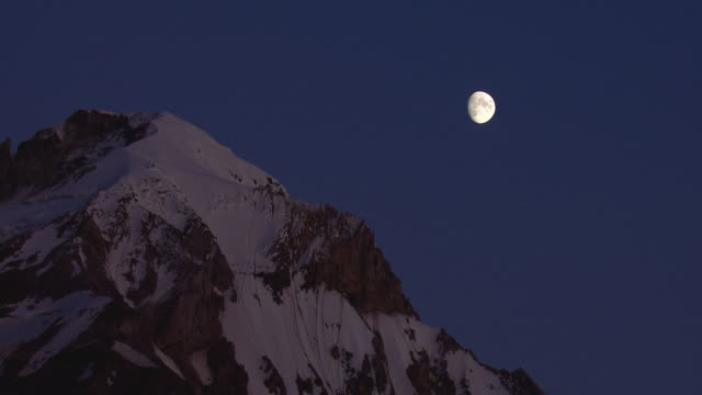 the moon hangs over the snowy peak of mt. hood. - mt hood stock videos & royalty-free footage