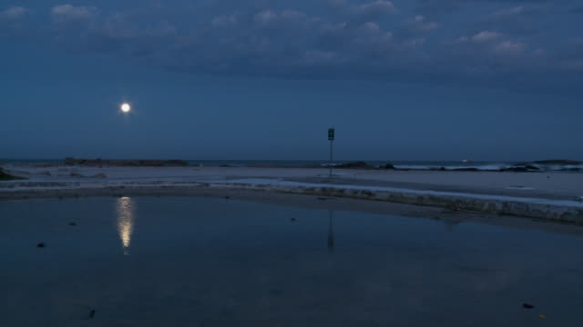 The moon illuminates the sky over the ocean at night. Available in HD.