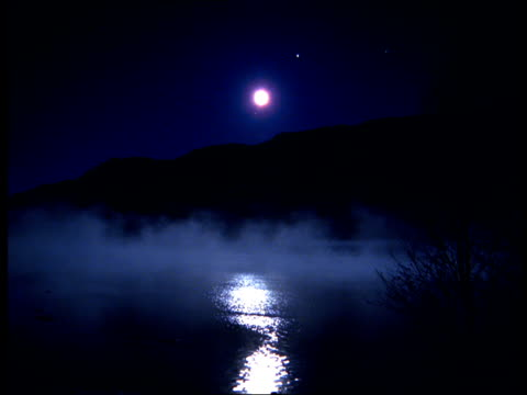 The moon reflects in the lake through the mist at night in Norway.