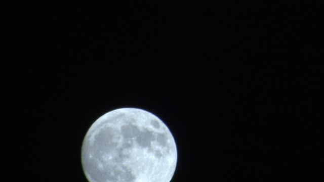 the moon rises against a black sky. - luna video stock e b–roll